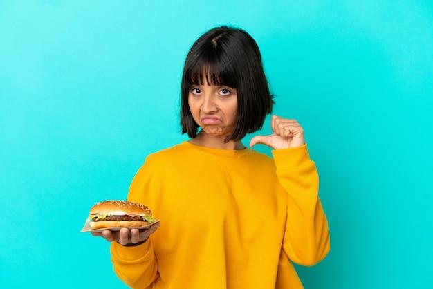 외진 배경 위에 햄버거를 들고 자랑스럽고 자기 만족스러운 젊은 갈색 머리 여자