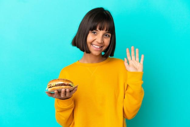 Молодая брюнетка женщина, держащая гамбургер на изолированном фоне, салютуя рукой с счастливым выражением лица