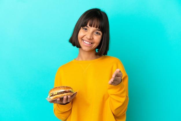 고립된 배경 위에 햄버거를 들고 좋은 거래를 성사시키기 위해 악수하는 젊은 브루네트 여성