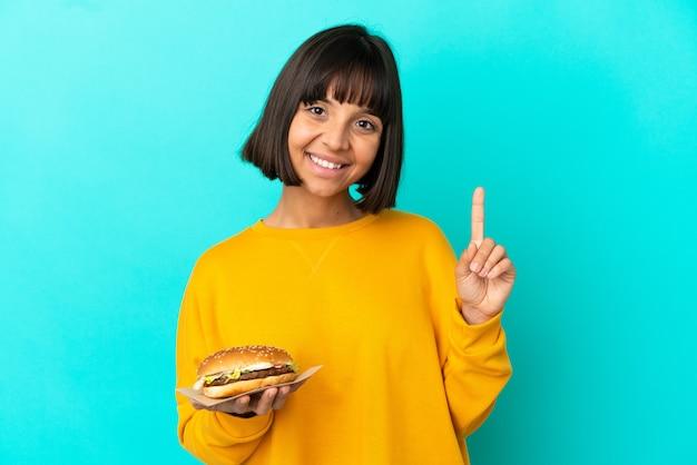 고립된 배경 위에 햄버거를 들고 있는 젊은 브루네트 여성이 최고라는 표시로 손가락을 들고 들어올린다