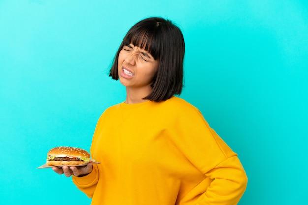 Молодая брюнетка женщина, держащая гамбургер на изолированном фоне, страдает от боли в спине из-за того, что приложила усилия