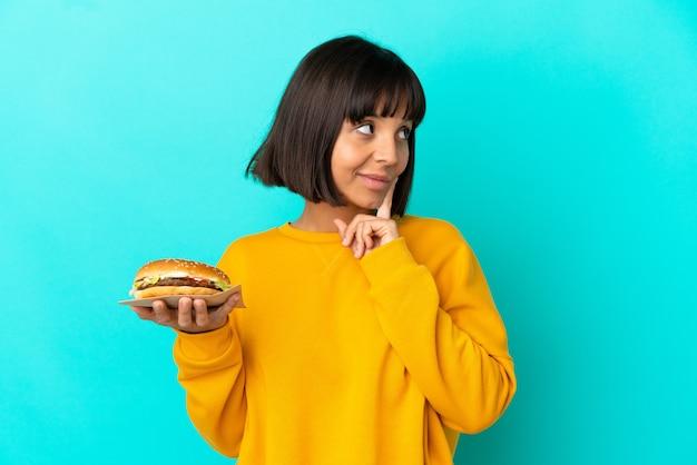 외진 배경 위에 햄버거를 들고 올려다보는 동안 아이디어를 생각하는 젊은 브루네트 여성