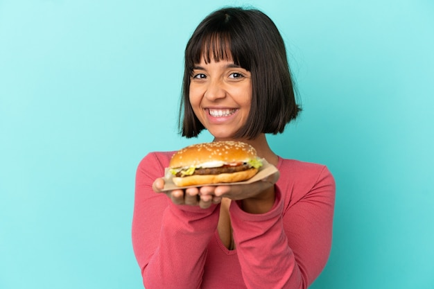 고립 된 배경 위에 햄버거를 들고 젊은 갈색 머리 여자