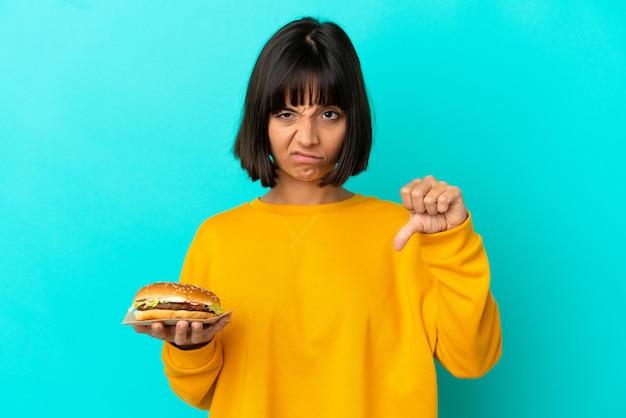부정적인 표현으로 아래로 엄지 손가락을 보여주는 고립 된 벽 위에 햄버거를 들고 젊은 갈색 머리 여자
