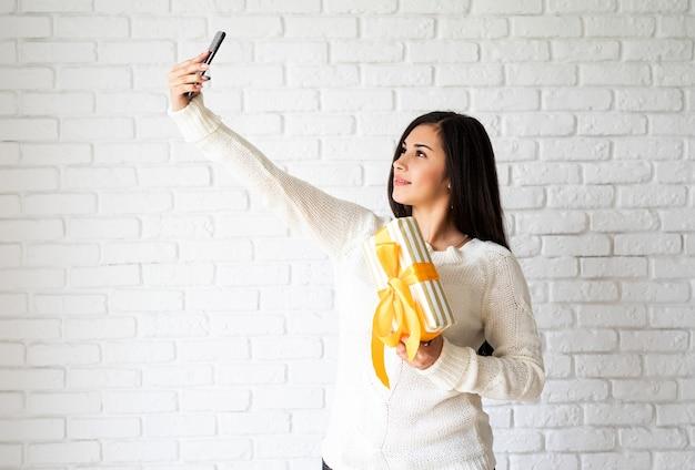 ギフトボックスを保持し、selfieを取る若いブルネットの女性