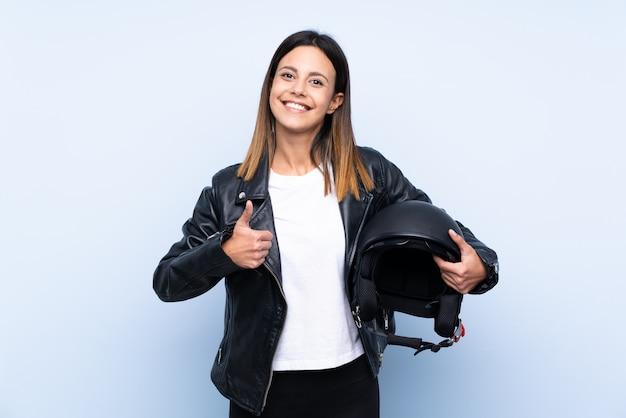 親指で青い壁にオートバイのヘルメットを保持している若いブルネットの女性