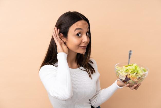 Молодая брюнетка женщина держит салат, слушая что-то, положив руку на ухо