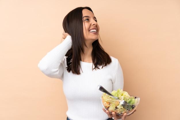 アイデアを考えてサラダを保持している若いブルネットの女性