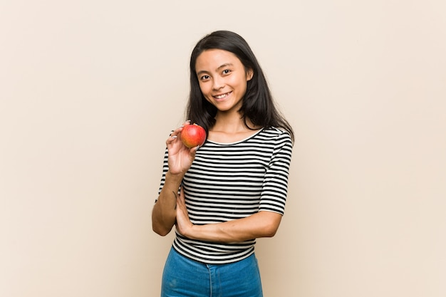 Young brunette woman holding an apple laughing and having fun