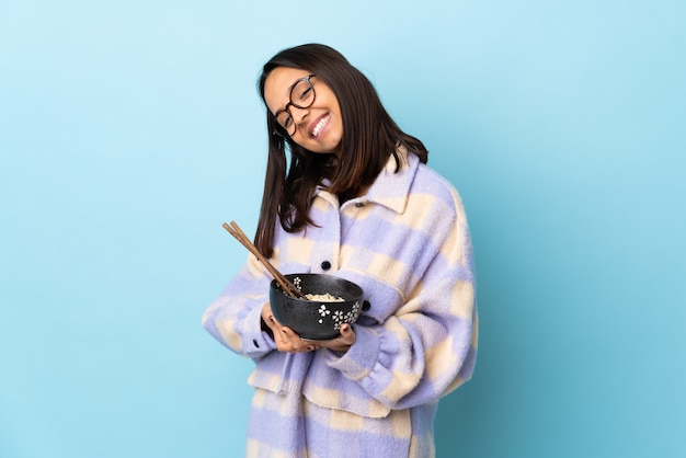 Young brunette woman holding a bowl full of noodles over isolated blue keeps palm together.