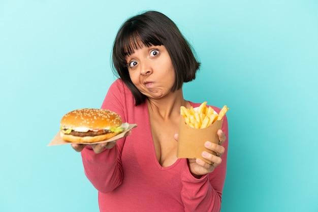 햄버거와 고립 된 파란색 배경 위에 튀긴 된 칩을 들고 젊은 갈색 머리 여자