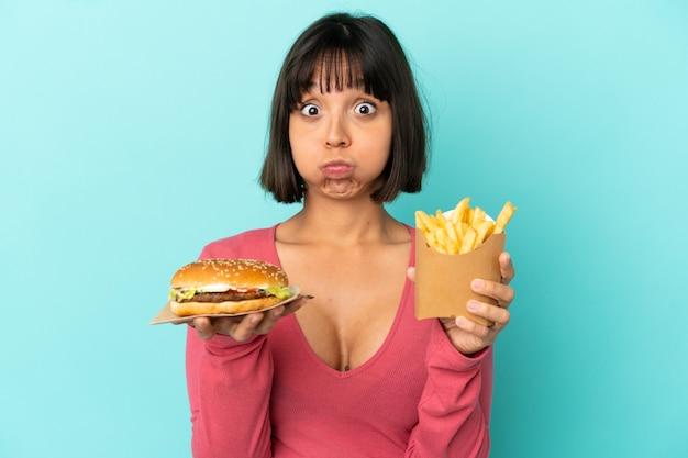 고립 된 파란색 배경 위에 햄버거와 튀긴 칩을 들고 젊은 갈색 머리 여자