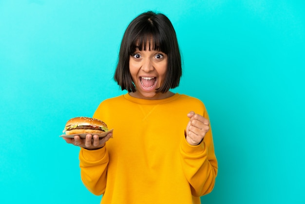 Young brunette woman holding a burger over isolated background celebrating a victory in winner position
