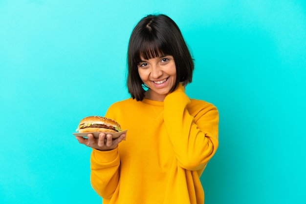 Young brunette woman holding a burger over isolated background laughing