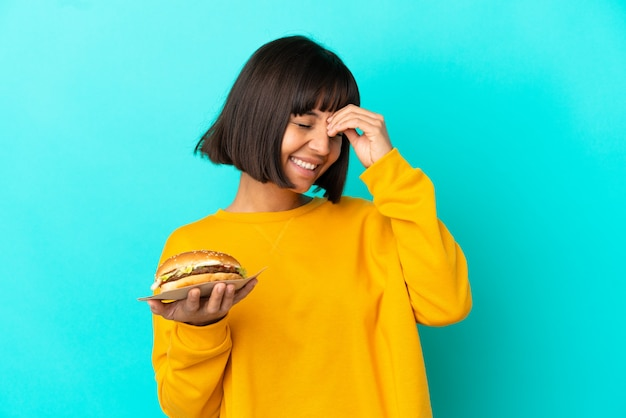 Young brunette woman holding a burger over isolated background smiling a lot
