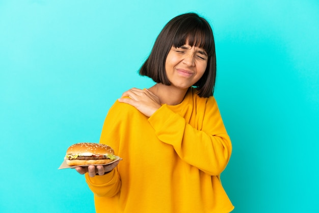 Young brunette woman holding a burger over isolated background suffering from pain in shoulder for having made an effort