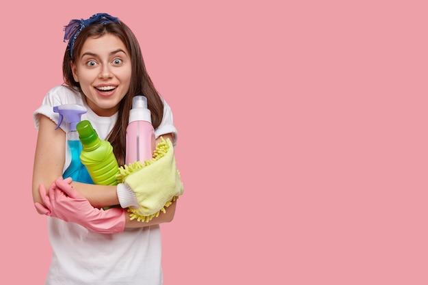 クリーニング製品を保持している若いブルネットの女性