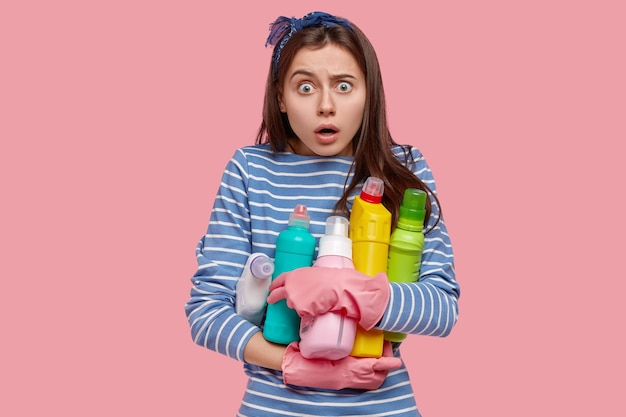 Young brunette woman holding cleaning products