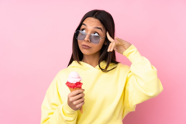 Young brunette woman holding a cornet ice cream over isolated pink wall having doubts and thinking