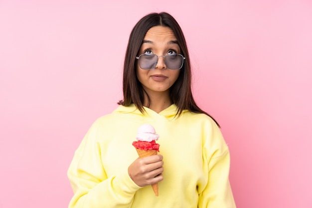 Young brunette woman holding a cornet ice cream over isolated pink wall making doubts gesture looking side
