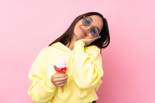 Young brunette woman holding a cornet ice cream over isolated pink wall making sleep gesture in dorable expression