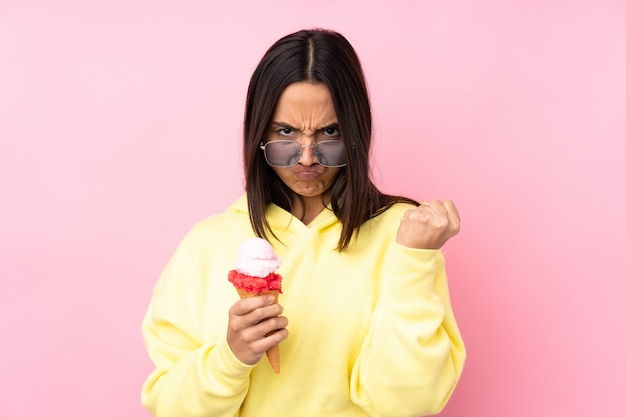 Young brunette woman holding a cornet ice cream with angry gesture