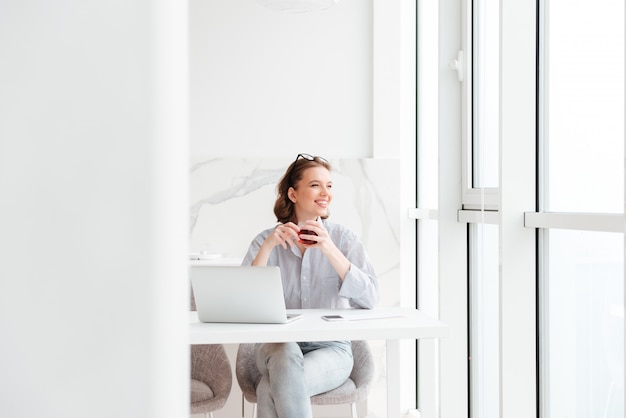 Young brunette woman holding cup of tea while sitting at kitchen and looking at large window