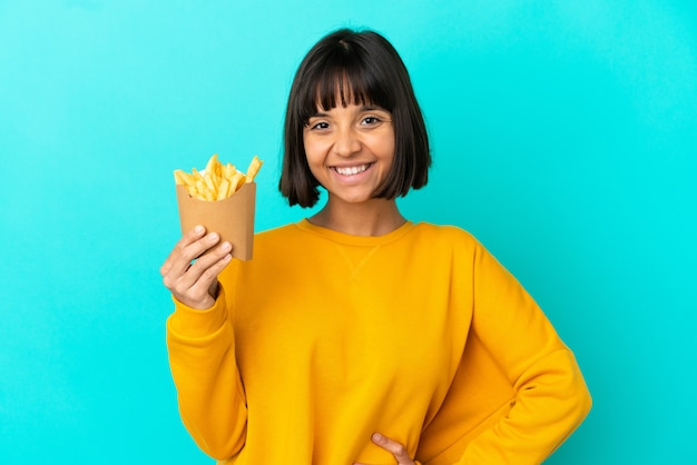 Young brunette woman holding fried chips over isolated blue background posing with arms at hip and smiling