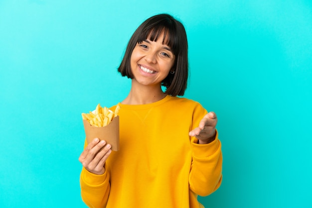 Young brunette woman holding fried chips over isolated blue background shaking hands for closing a good deal