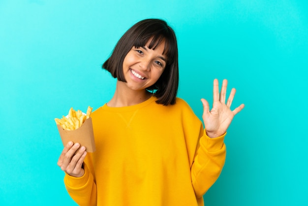 고립된 파란색 배경 위에 튀긴 칩을 들고 손가락으로 다섯을 세는 젊은 브루네트 여성