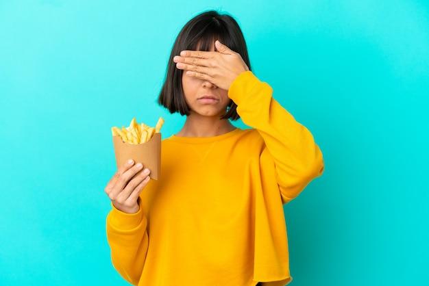 손으로 눈을 덮고 고립 된 파란색 배경 위에 튀긴 칩을 들고 젊은 갈색 머리 여자. 뭔가 보고 싶지 않아
