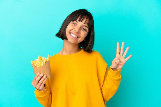 Молодая брюнетка женщина, держащая жареные чипсы на изолированном синем фоне, счастлива и считает четыре пальцами