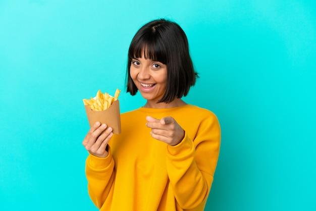Молодая брюнетка женщина, держащая жареные чипсы на изолированном синем фоне, указывая вперед с счастливым выражением лица