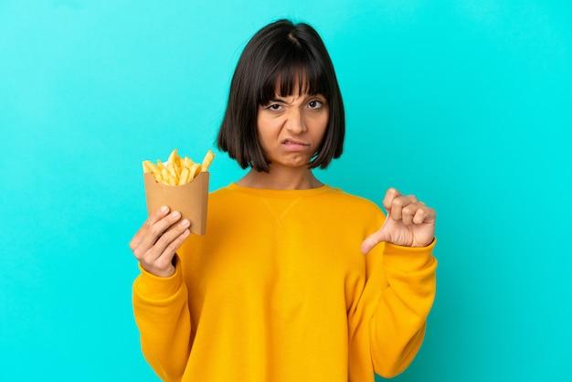 부정적인 표정으로 엄지손가락을 아래로 보여주는 고립된 파란색 배경 위에 튀긴 칩을 들고 젊은 갈색 머리 여자
