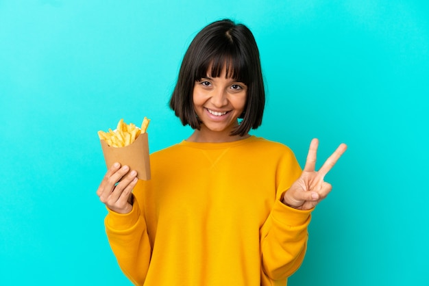 Молодая брюнетка женщина, держащая жареные чипсы на изолированном синем фоне, улыбается и показывает знак победы