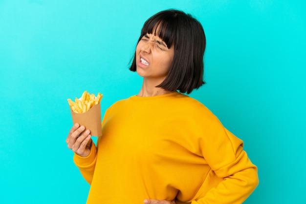 Молодая брюнетка женщина, держащая жареные чипсы на изолированном синем фоне, страдает от боли в спине из-за того, что приложила усилия