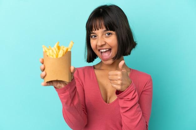 고립 된 파란색 배경 위에 튀긴 칩을 들고 젊은 갈색 머리 여자