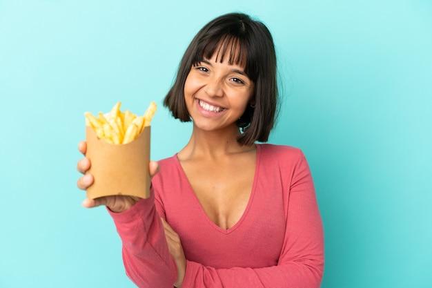 Молодая брюнетка женщина, держащая жареные чипсы на изолированном синем фоне