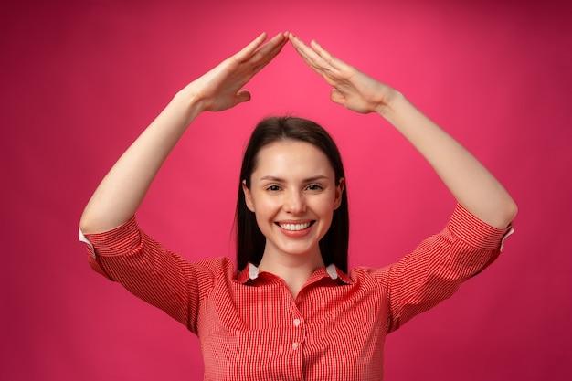 ピンクの背景に屋根のように頭の上に手を保持している若いブルネットの女性