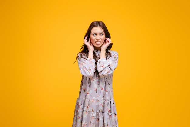 Young brunette woman holding her ears irritated with noise isolated over yellow background