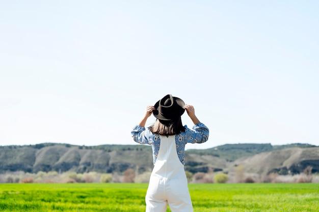 Молодая брюнетка женщина держит шляпу на спине в поле
