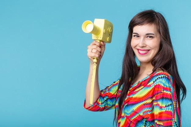 彼女の手で青い壁にポーズをとって黄色のカムコーダーのモデルを保持している若いブルネットの女性