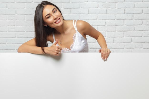 Young brunette woman holding large blank white board with copy space
