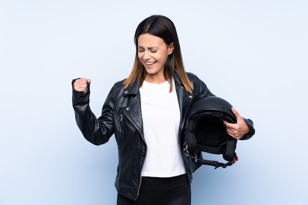Young brunette woman holding a motorcycle helmet over blue wall celebrating a victory