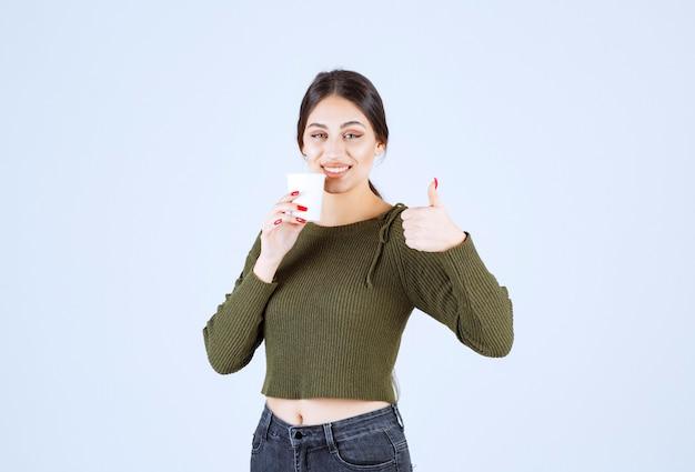 Giovane donna castana che tiene tazza di plastica e dà i pollici in su.