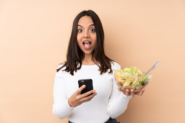 Young brunette woman holding a salad surprised and sending a message