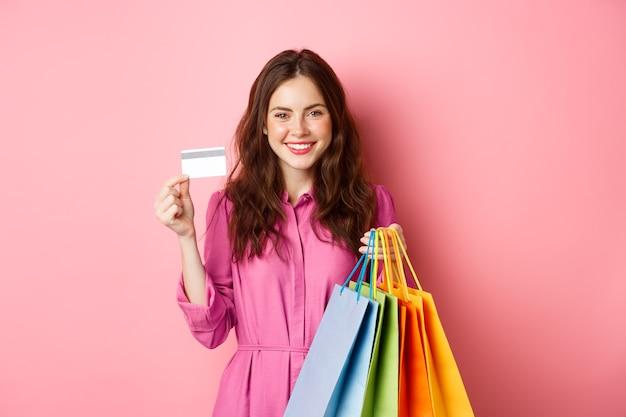 ショッピングバッグを持って、プラスチックのクレジットカードを見せて、ピンクの壁に立って笑っている若いブルネットの女性。