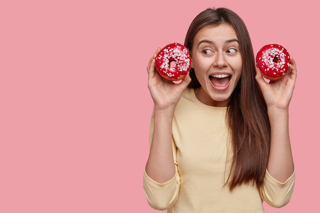 おいしいドーナツを保持している若いブルネットの女性