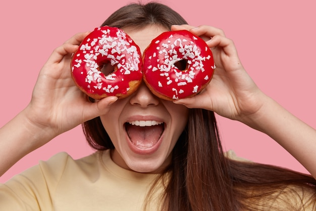 Young brunette woman holding tasty donuts