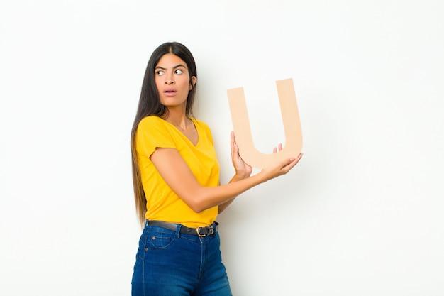 単語または文を形成するアルファベットのuの文字を保持している若いブルネットの女性